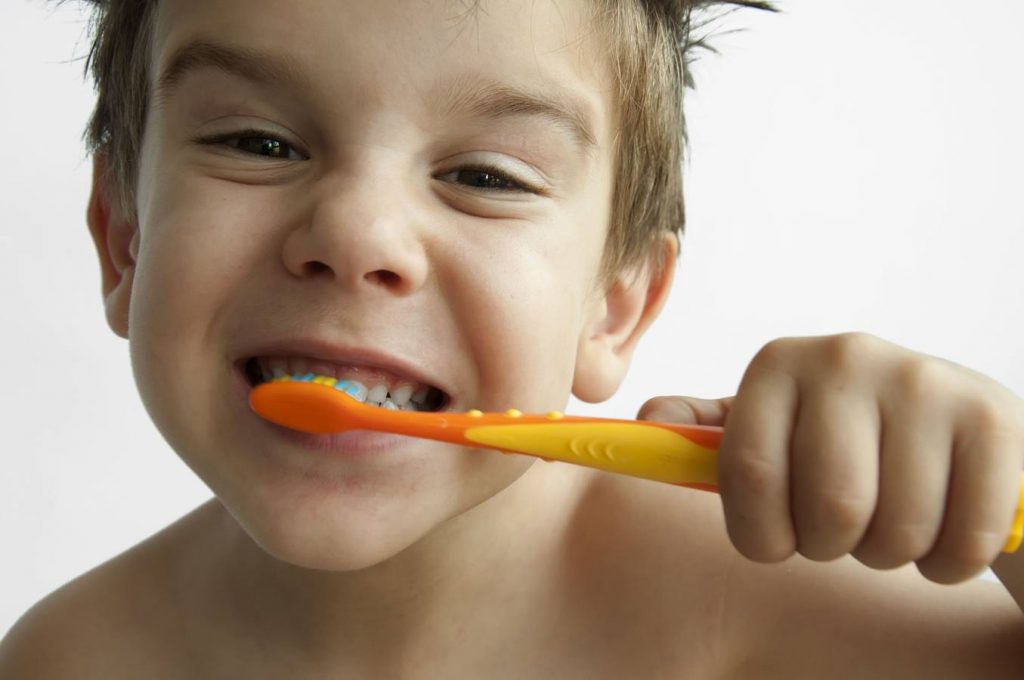 Boy washing teeth with toothbrush