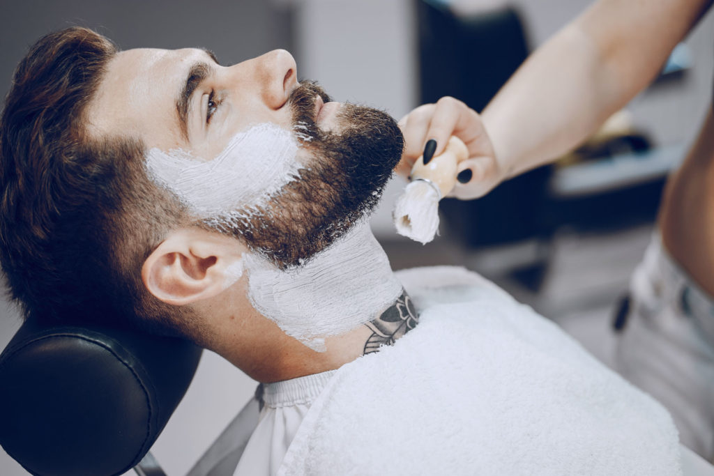 handsome young bearded guy sitting in an armchair in a beauty salon and the girl around him smears his beard with cream