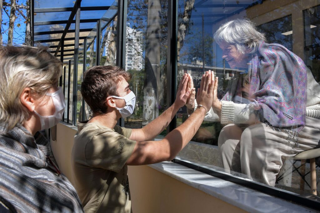 Brazilian Alexandre Schleier (C) speaks with his 81-year-old grandmother Olivia Schleier (R), next to his mother Eunice Schleier (L), through a window at the Premier Hospital, in Sao Paulo, Brazil, on May 28, 2020. - The hospital does not have any case of COVID-19 but does not permit visits to prevent contagions of the new coronavirus. (Photo by NELSON ALMEIDA / AFP)
